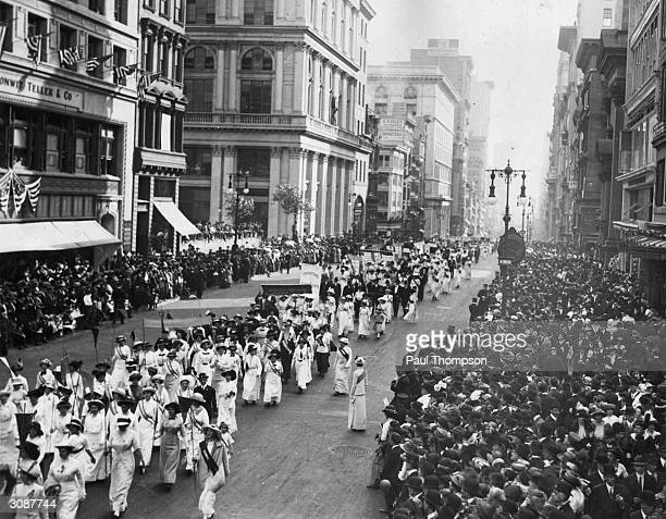 Crowds line the sidewalks to watch a Women's Suffrage Movement march through New York City.