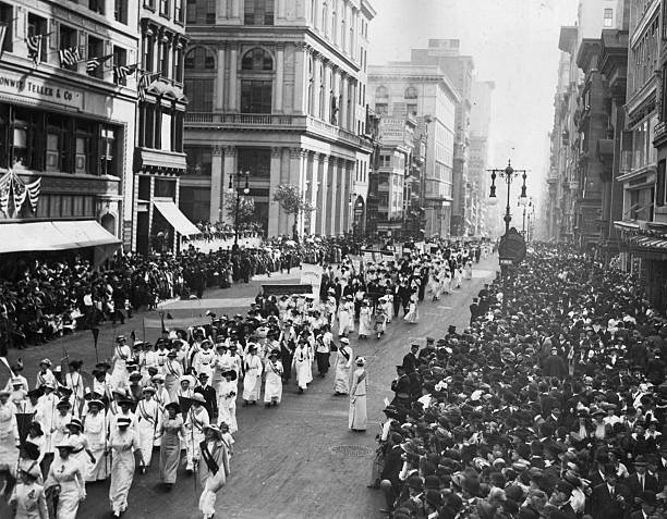 Crowds line the sidewalks to watch a Women's Suffragette...