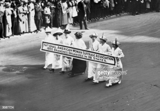 Members of the National American Woman Suffrage Association marching with a banner which publicises their '1000 branches organized in 38 states' at...