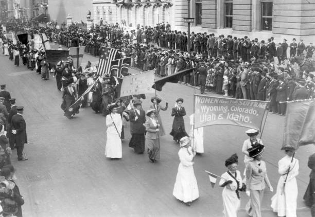 Suffragettes carrying a banner announcing that 'Women...