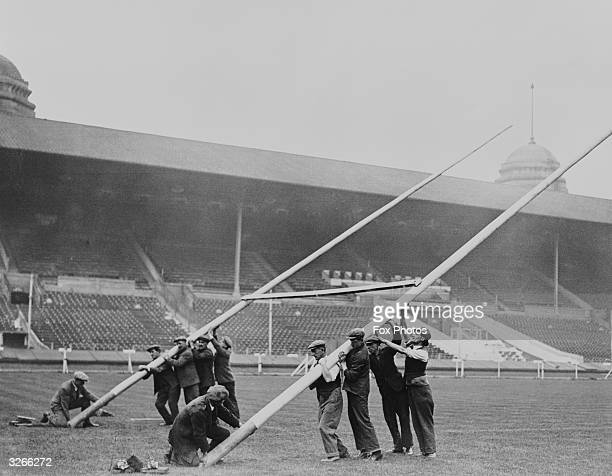 Workmen raise the rugby goalposts at Wembley Stadium in preparation for the Rugby League Cup Final