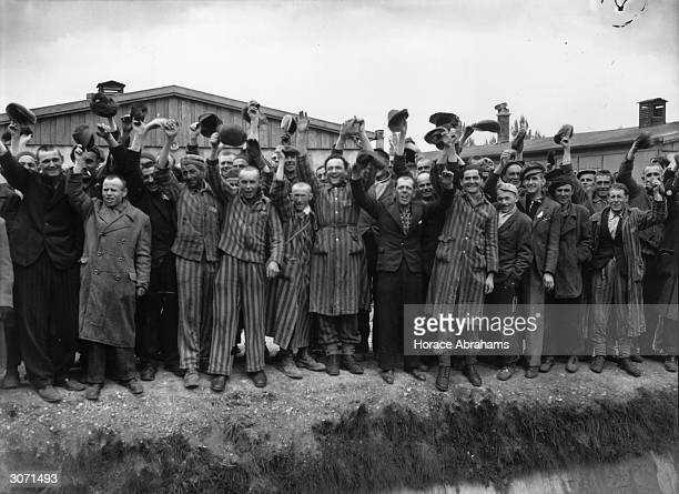 Liberated prisoners from Dachau the German concentration camp wave in joy Those wearing striped uniforms are political prisoners whose fate was...