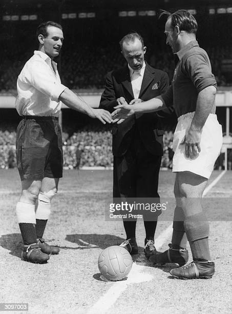 Belgian referee L Baert with the England captain George Hardwick and French captain Oscar Heisserer before the match at Highbury in London England...