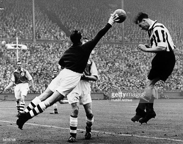 Arsenal goalkeeper George Swindin reaches to collect the ball as it leaves Newcastle United striker Jackie Milburn's head during the 1952 FA Cup...