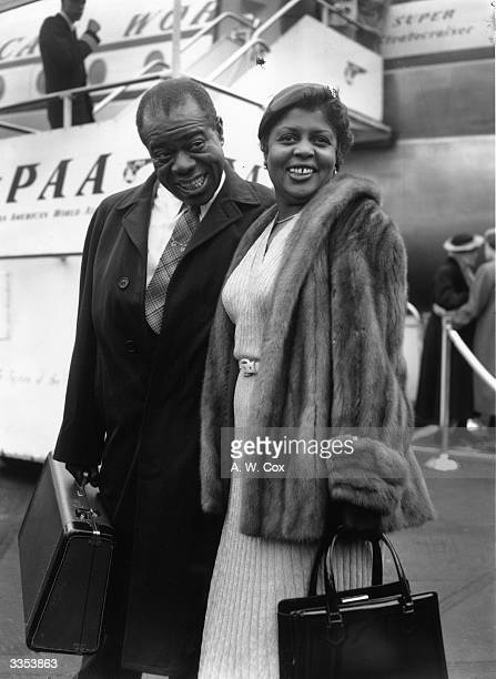 American jazz musician Louis Armstrong with his wife Lucille at London Airport