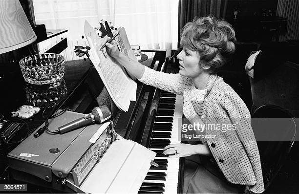 Singer Petula Clark at the piano working on the score of a song