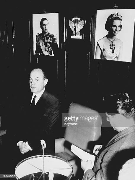 Greek Prime Minister George Papadopoulos speaking at a press conference with pictures of King Constantine and Queen Anne Marie on the wall behind him