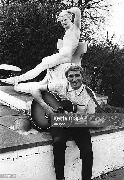 Yodelling English pop star Frank Ifield, the biggest selling star in the UK during the early 1960's, strums a guitar in the garden of his new home in...