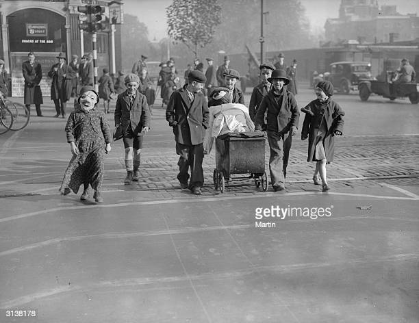 Children pushing a pram containing a guy to celebrate Guy Fawkes are using a 'pedestrian lane' in Kennington Road south London a new concept in road...