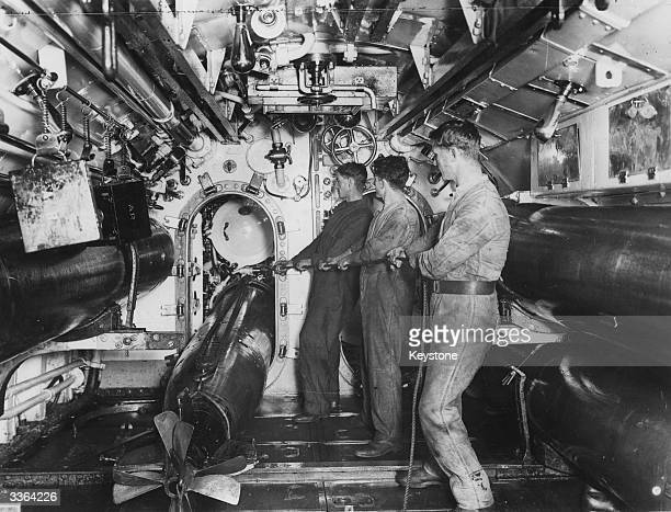 Young naval ratings on a British submarine during World War II load a torpedo into the launch tube in anticipation of attack by enemy vessels