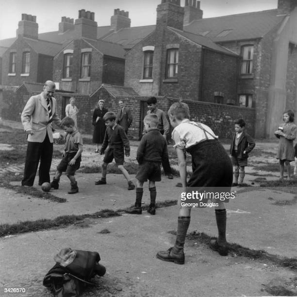A group of young boys practise their football skills on the Middlesbrough streets with their local team idol Wilf Mannion Original Publication...