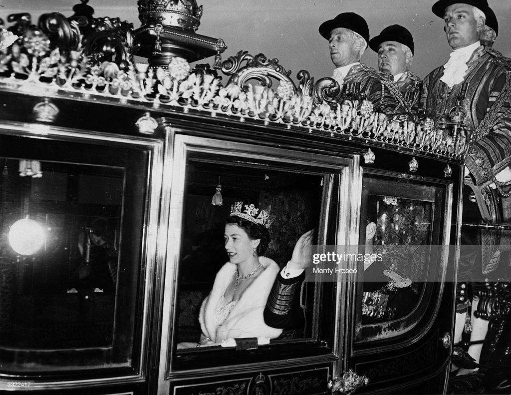 Queen Elizabeth II in the traditional Irish state coach travelling to Westminster for her first state opening of parliament as the crowned sovereign.