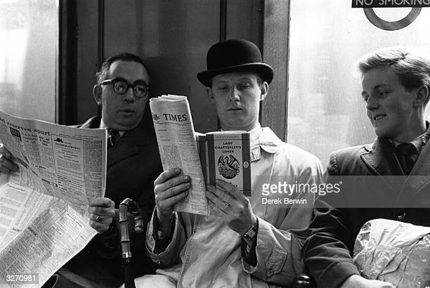 Fox photographer George Freston poses as a commuter on the London Underground reading a copy of D H Lawrence's novel 'Lady Chatterley's Lover' on the...