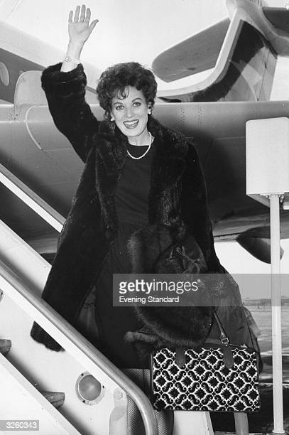 Irish actress Maureen O'Hara boarding an aeroplane