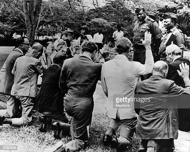 Idi Amin Dada, the president of Uganda, takes the oath of allegiance of twelve British ex-army officers, In Kampala, who are to serve in Amin's armed...