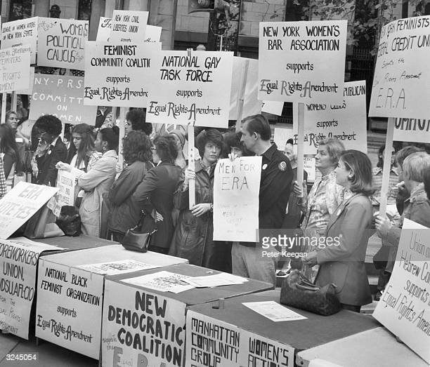 People hold signs in favor of the Equal Rights Amendment to the New York Constitution at a rally in Bryant Park New York City
