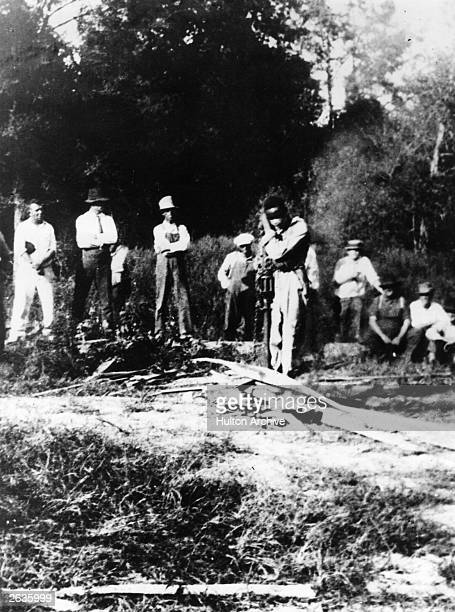 A gang of white men gather around J D Ivy a black man they have blindfolded and tied to a stake in a forest in Georgia USA Kindling is piled round...