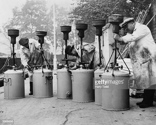 A group of men cleaning fog lamps used during London's notorious foggy weather