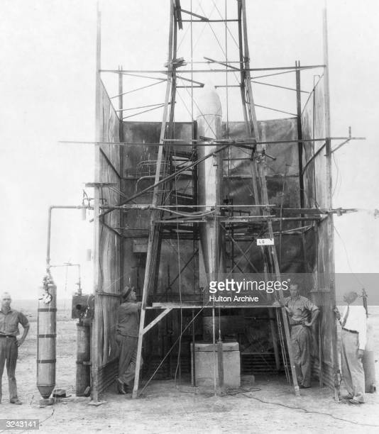 American physicist Dr Robert H Goddard stands with his crew inspecting a rocket set in a launching tower converted from a windmill