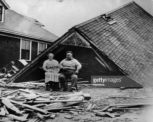 Couple sitting amongst the remains of their home at Highland Park, Rhode Island, USA, after a 100-mile-an-hour swept the Atlantic coast of North...