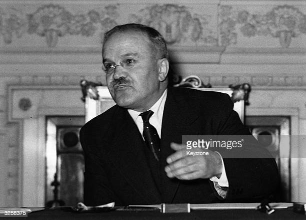 Viatcheslav Mikhailovitch Molotov Soviet politician and diplomat at his desk answering press questions at the Soviet Embassy
