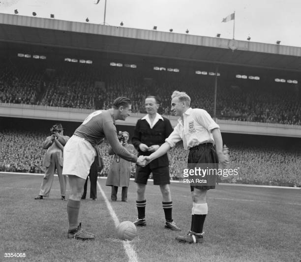 England captain Billy Wright right shakes hands with French inside right and captain Jean Baratte before playing a Festival of Britain International...