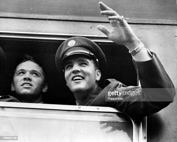 3rd October 1958 Bremerhaven Germany US rock and roll singer Elvis Presley waves to newsmen and fans on arrival on a troopship and boarding a train...