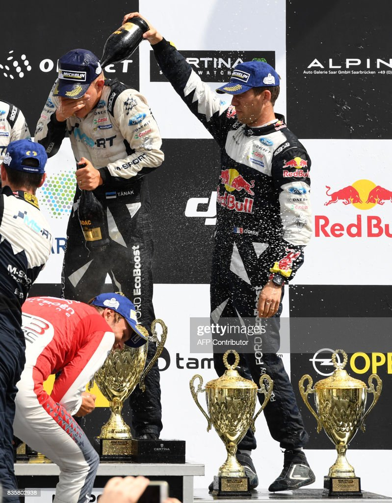 3rd place Sebastien Ogier (R) and his co-driver Julien Ingrassia of France celebrate during the flower ceremony after the WRC Germany on August 20, 2017 in Neunkirchen, western Germany. /
