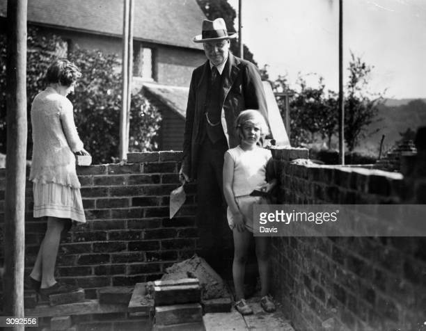 British Chancellor of the Exchequer Winston Leonard Spencer Churchill enlists the help of his two daughters Sarah and Mary in building the brick wall...
