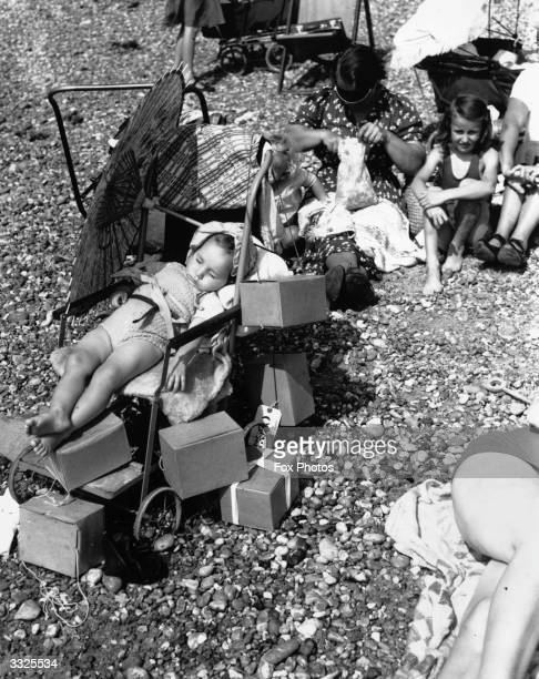 A sunbathing baby taking a nap on Brighton Beach surrounded by boxes of gas masks