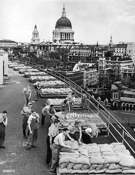 Office workers lend a hand to piling sandbags around the roof of the Unilever Building in London's Blackfriars at the start of World War II The dome...