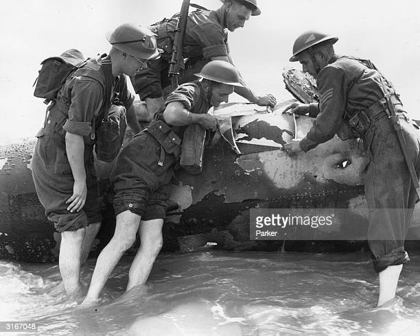 British soldiers paddling in the sea to cut the running boar insignia from a crashed German aircraft at Sandwich in Kent