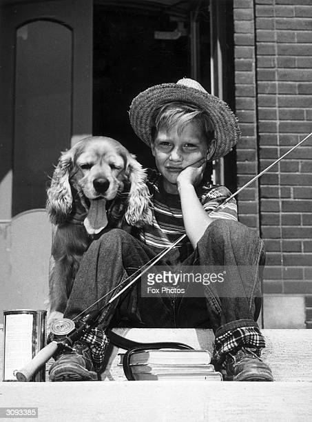 A little boy sitting beside his dog wearing jeans and a straw hat his fishing rod leaning against him at Alderwood Ontario Canada He is looking...