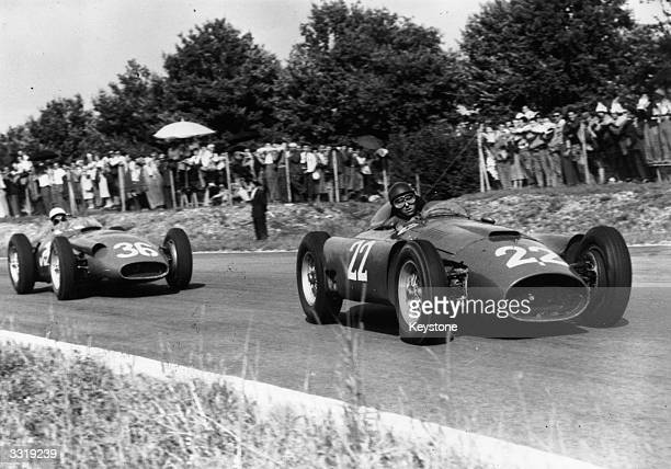 World champion Argentinian racing driver Juan Manuel Fangio in action in a Ferrari leading Stirling Moss in a Maserati at the 1956 Italian Grand Prix...