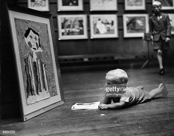 22month old Barry Newsam inspects one of the paintings on display at the National Exhibition of Children's Art at the Royal Institute Galleries
