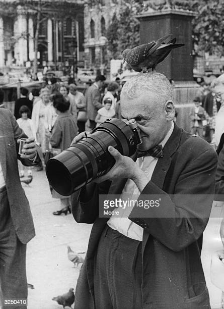 American press photographer Weegee in Trafalgar Square London with a pigeon on his head Weegee was famous for his distorted photographs which turned...