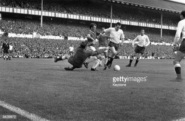 Tottenham Hotspur goalkeeper Pat Jennings dives at the feet of Arsenal inside right Tommy Baldwin only for the ball to be cleared by Spurs captain...