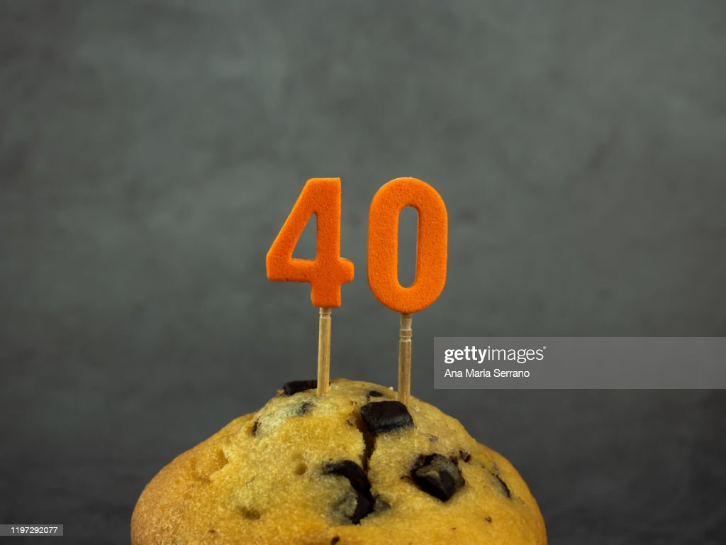 40th Birthday candles in a cupcake with chocolate pieces on a dark background : ストックフォト
