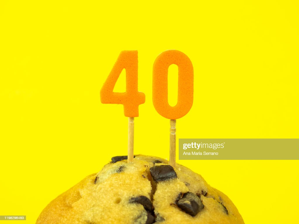 40th Birthday candles in a cupcake with chocolate pieces on a yellow background : ストックフォト