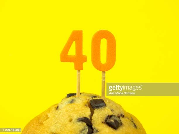 40th birthday candles in a cupcake with chocolate pieces on a yellow background - 40歳の誕生日 ストックフォトと画像