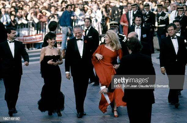The Birthday Party Arrivée souriante en bas des marches du Palais des festivals d'Yves MONTAND avec sa compagne Carole AMIEL et Catherine DENEUVE