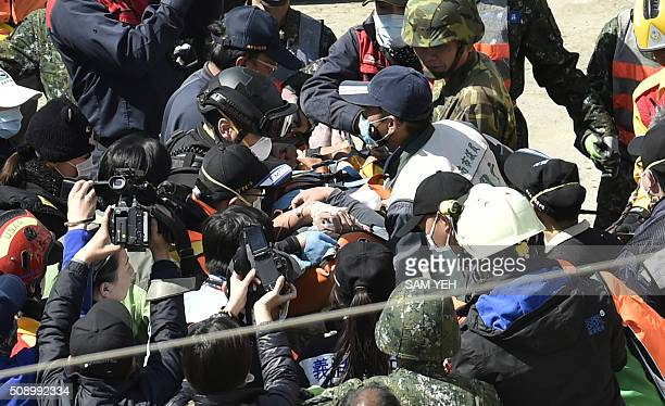 TOPSHOT A 40yearold man identified by local media as Lee Tsungtian is checked by medical personnel after being rescued from the rubble at the WeiKuan...