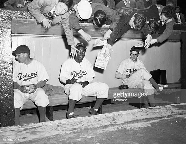 New York, NY: Youthful Brooklyn Dodger's rooters and fans, reach over from behind the dugout at Ebbets field today, trying to get an autograph from...