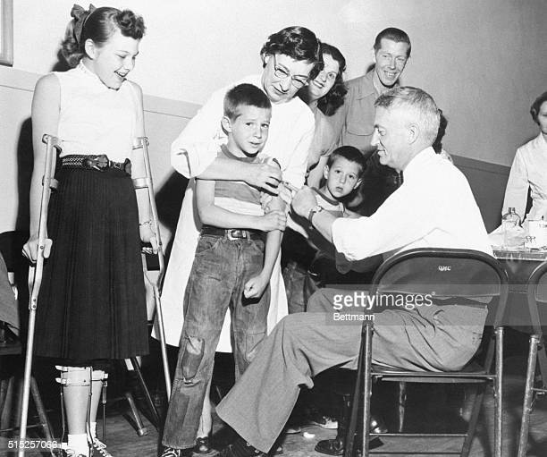 4/16/1955San Diego California Dr William S Burgoyne gives a shot of the Salk antipolio vaccine to Michael Urnezis while the boy's sister Joanne a...
