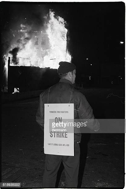 4/16/1981Yonkers NY A striking Yonkers firefighter carries his sign in front of firehouse here early 4/16 as building across street blazes A skeleton...