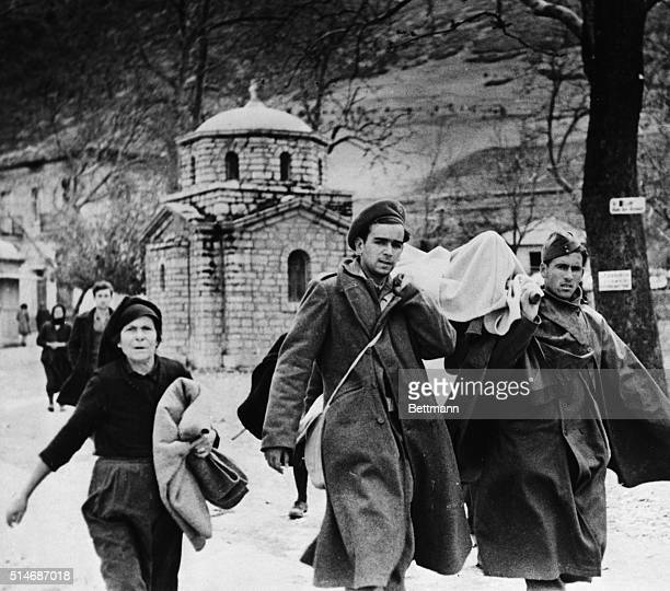 4/17/1948Kalavrita Greece Regular Greek Army troops carry one of the hundreds of persons wounded when 1000 guerillas sacked the town killing 40...