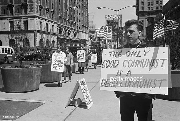 4/17/1965New York New York AntiCommunist picket stands solidly opposed to young protesters maintaining a silent shuffling vigil against violence in...