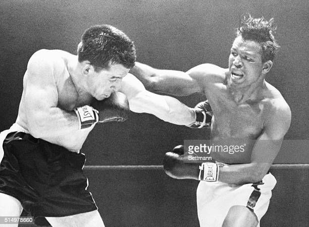 Middleweight champion Sugar Ray Robinson throws a right over the head of Rocky Graziano who scores with a hard left to the ribs of Sugar Robinson...