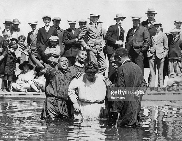 4/19/1927Boston MA Photo shows Bishop J Harris baptising sister Elsie Hoyt assisted by other clergymen as a fitting ceremonial for the Easter season...