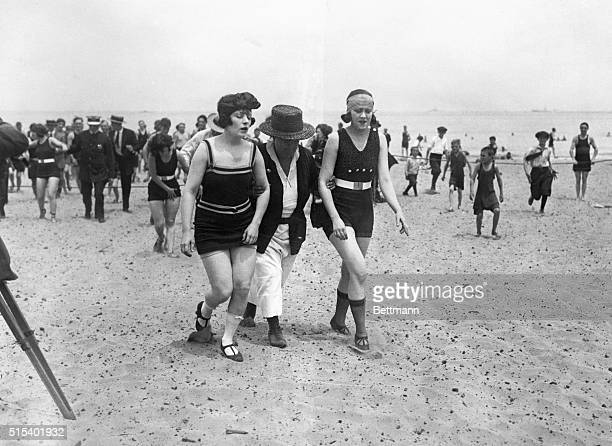 4/1922Chicago Illinois Two of the bathers being escorted off the beach by a police woman The bathers were breaking a law banning abbreviated bathing...